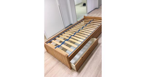 Eénpersoons bed met grote laden er onder