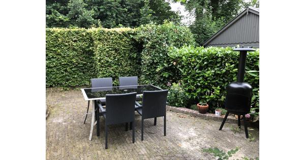 Lichte tuintafel met zwart glazen blad