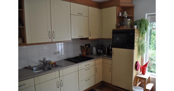 Keuken met koelkast, oven, keukenboiler en kleine vaatwasser